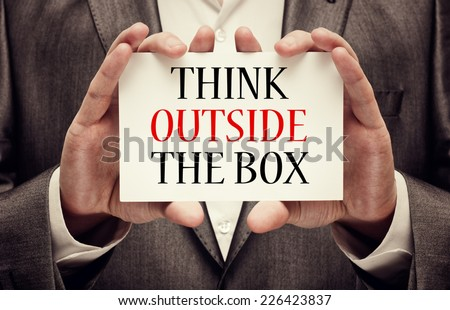 Think outside the box. Businessman holding a signboard with a message text written on it - stock photo