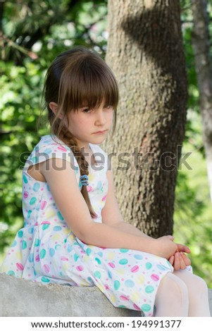 Thinked little girl outside - stock photo