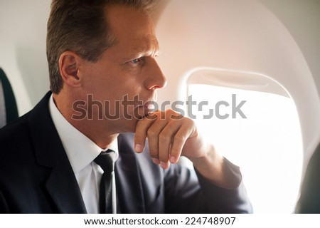 Thinking about solutions. Thoughtful mature businessman sitting at his seat in airplane and looking through airplane window - stock photo