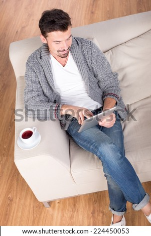 Thinking about solutions. Top view of handsome young man lying on the couch at his apartment - stock photo