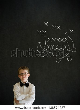 Thinking boy dressed up as business man with chalk American football strategy on blackboard background - stock photo