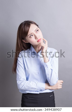 Thinking business woman and look copy space isolated on grey background with finger at face, asian beauty - stock photo