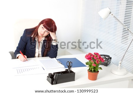thinking  business woman with documents sitting in a comfortable modern office - stock photo