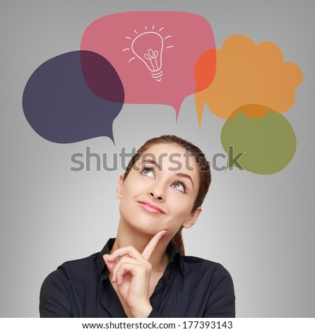 Thinking business woman with idea bulb in bubble on grey background - stock photo