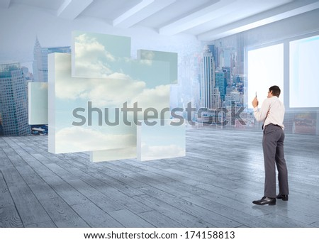 Thinking businessman holding pen against room with cityscape and panes showing sky - stock photo