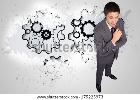 Thinking businessman holding pen against splash on wall revealing cogs and wheels - stock photo