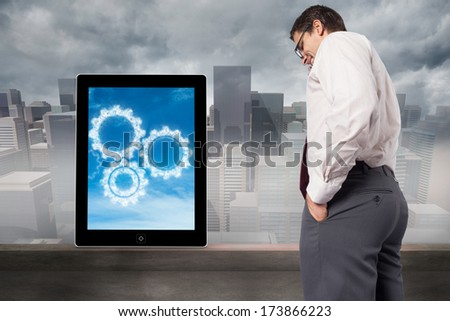 Thinking businessman touching his glasses against cityscape in the fog - stock photo