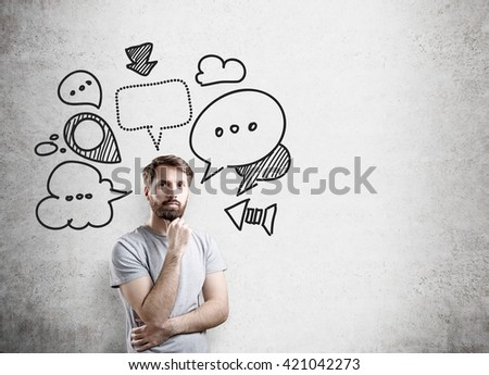 Thinking businessman with speech and thought bubbles on concrete wall - stock photo