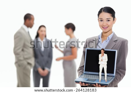 Thinking businesswoman against businesswoman smiling showing a laptop screen with coworkers in the background - stock photo