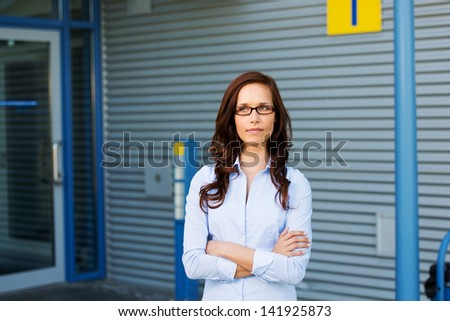 Thinking businesswoman looking at something with her arms crossed - stock photo