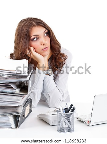 Thinking businesswoman sitting behind the desk in the office - stock photo