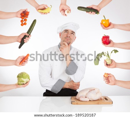Thinking chef, hand with vegetable and raw chicken. - stock photo