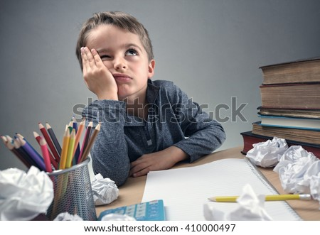 Thinking child bored, frustrated and fed up doing his homework - stock photo