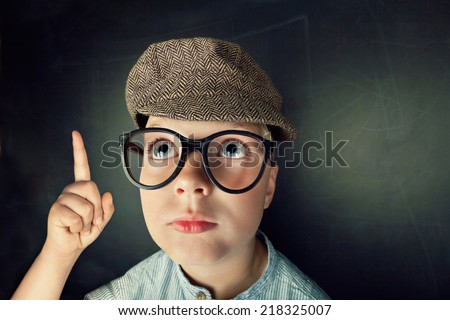 thinking Child with thick eyeglasses with blackboard in background - stock photo