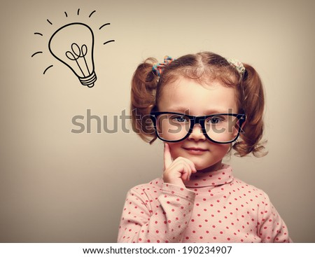 Thinking happy kid in glasses with idea bulb above the head - stock photo