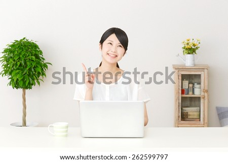 thinking Japanese woman with PC - stock photo