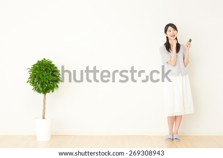 thinking Japanese woman with the smart phone - stock photo