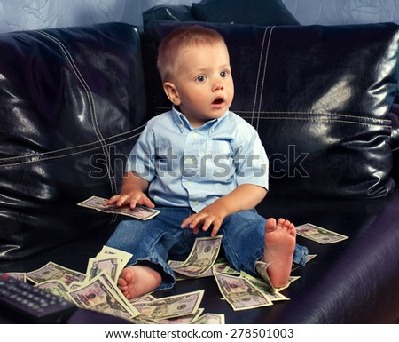 Thinking little boy with fake money - stock photo