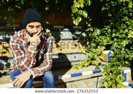 Thinking man by green plans . Multiracial hipster university college student pensive and contemplating looking up at green plants background. Asian Caucasian, 20s.  - stock photo