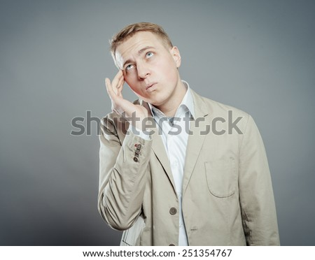 Thinking man isolated on gray background. Closeup portrait of a casual young pensive businessman looking up at copyspace. - stock photo