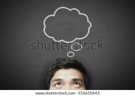 Thinking man with thinking bubble on blackboard background. - stock photo
