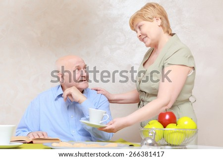 Thinking of each other. Elderly woman bringing a cup of tea to her husband reading a book by the table - stock photo