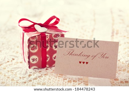 Thinking of you message written on a card with a hand crafted present box  - stock photo