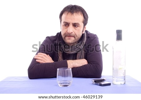 Thinking sad looking man sitting at the table isolated on white background - stock photo