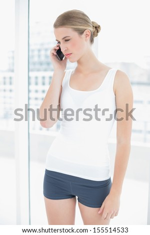 Thinking sporty woman in bright sports hall having a phone call - stock photo