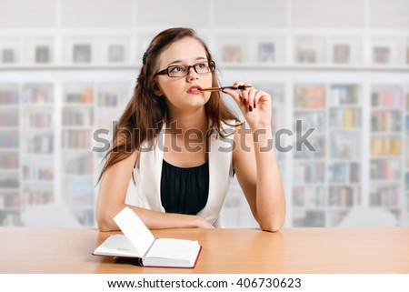 thinking student girl sitting at desk in the library on white background - stock photo