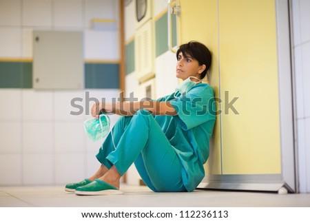 Thinking surgeon sitting on the floor in a hallway - stock photo