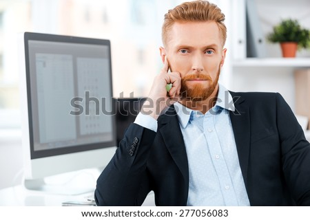Thinking up his next business move. Confident young bearded businessman looking at camera while sitting at his working place - stock photo