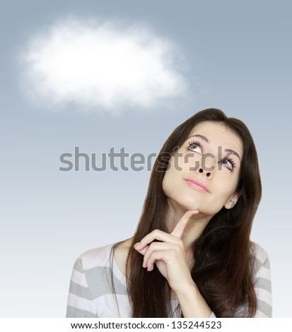 Thinking woman looking up with white cloud above on blue background - stock photo