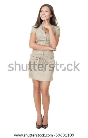 Thinking woman standing in full length isolated on white background in beige neutral dress. Mixed asian / caucasian young woman. - stock photo