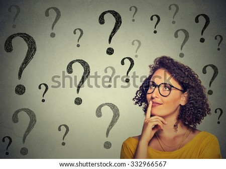 Thinking young business woman in glasses looking up at many question marks isolated on gray wall background - stock photo