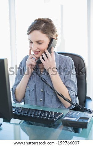 Thinking young businesswoman phoning while sitting a desk in office - stock photo