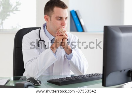 Thinking young doctor looking at his screen - stock photo
