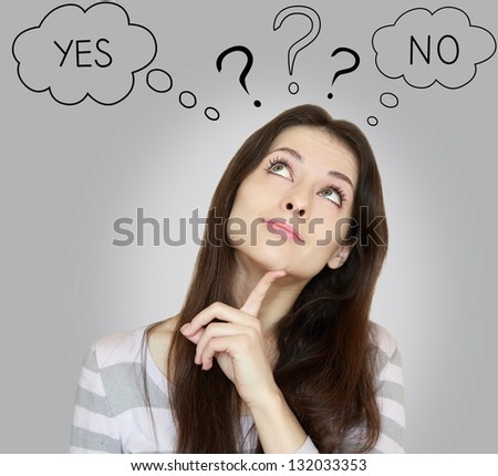 Thinking young woman with yes or no choice looking up with finger at face on grey background - stock photo