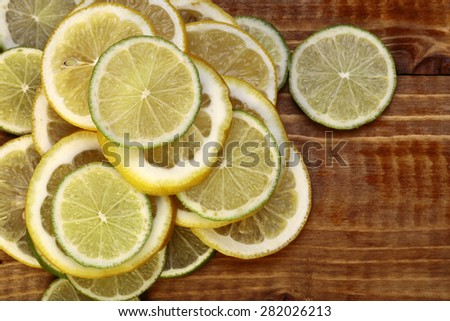 Thinly sliced round pieces of yellow juicy delicious fresh lemon lying on a brown wooden table top background copy space, horizontal photo - stock photo