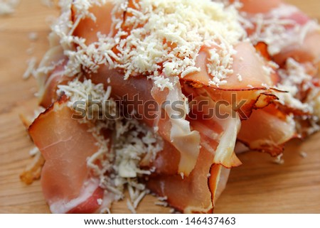 Thinly sliced Tyrolean Smoked bacon (ham) with grated spicy horseradish - stock photo