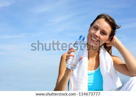 Thirsty fitness girl holding bottle of water - stock photo