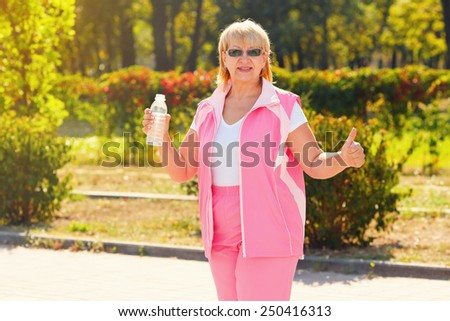 Thirsty fitness woman holding bottle of water. Senior woman resting after exercises. Adult woman in a city park in the morning after a good workout. Drink water after exercise. Woman outdoor. - stock photo