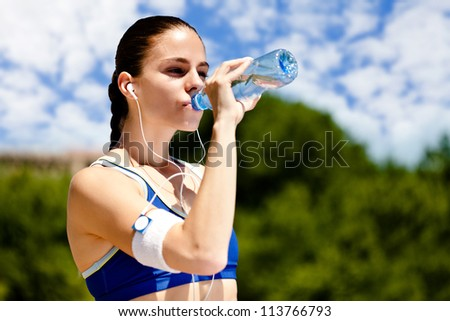 thirsty sporty woman drinking water after training - stock photo