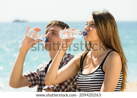 Thirsty young couple taking with pleasure a refreshing drink of water at sunny day - stock photo