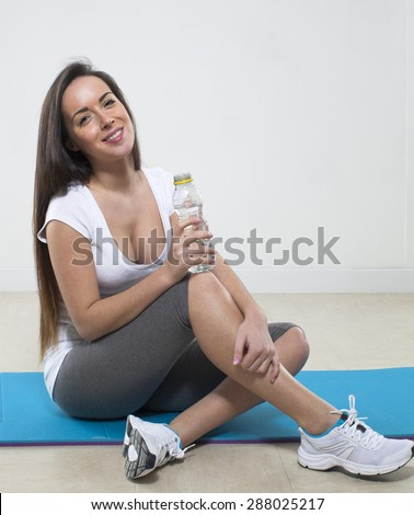 thirsty young fitness woman sitting on an exercise mat with gym clothes and bottle of water  - stock photo