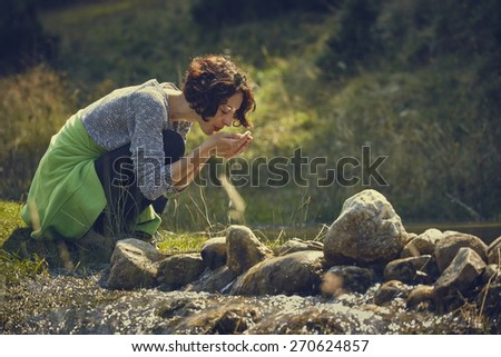 Thirsty young lady drinking from her palms fresh water of a mountain stream on a sunny summer day. - stock photo