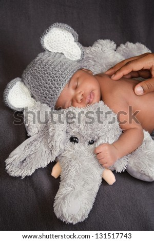 Thirteen day old newborn baby boy in a grey crocheted elephant hat, sleeping on a plush elephant. His father is touching his back and the baby has a sweet look of contentment. - stock photo