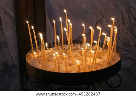 Thirty burning beeswax candles in a church - stock photo