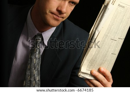 Thirty something business man with newspaper over black. - stock photo
