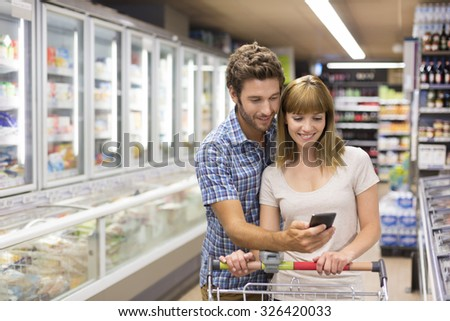 Thirty-year-old couple using mobile phone in supermarket - stock photo